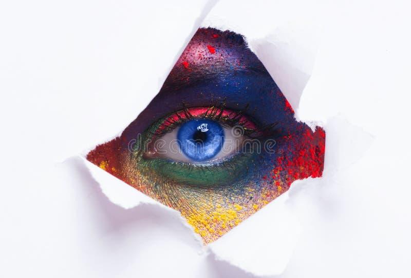 Oeil femelle lumineux regardant par le trou en papier photo stock