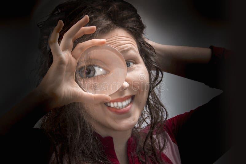 Oeil femelle regardant par la fin de loupe  photographie stock libre de droits