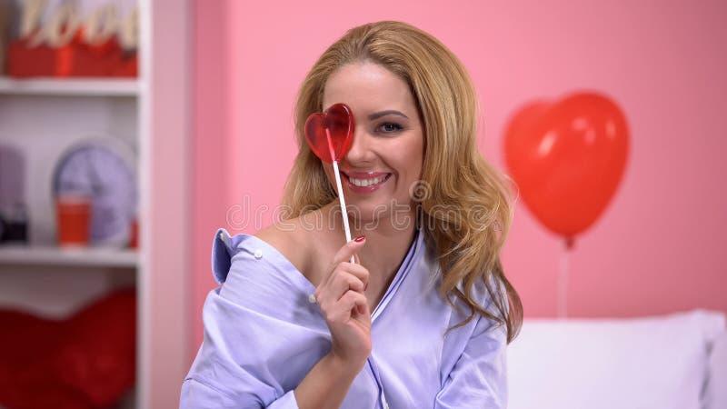 Oeil fermant de dame blonde séduisante avec la lucette en forme de coeur, souriant à la caméra photographie stock libre de droits