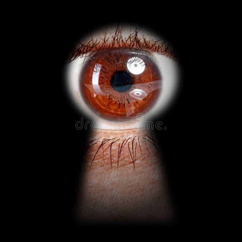 Oeil jetant un coup d'oeil par un trou de la serrure images libres de droits