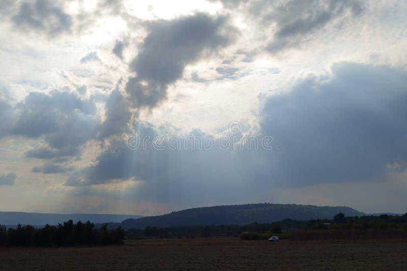 Oeil merveilleux Un pilier des rayons de soleil par des nuages de tonnerre photographie stock