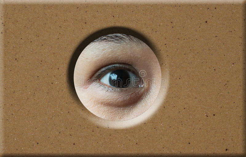 Oeil regardant par le trou dans la brique image libre de droits