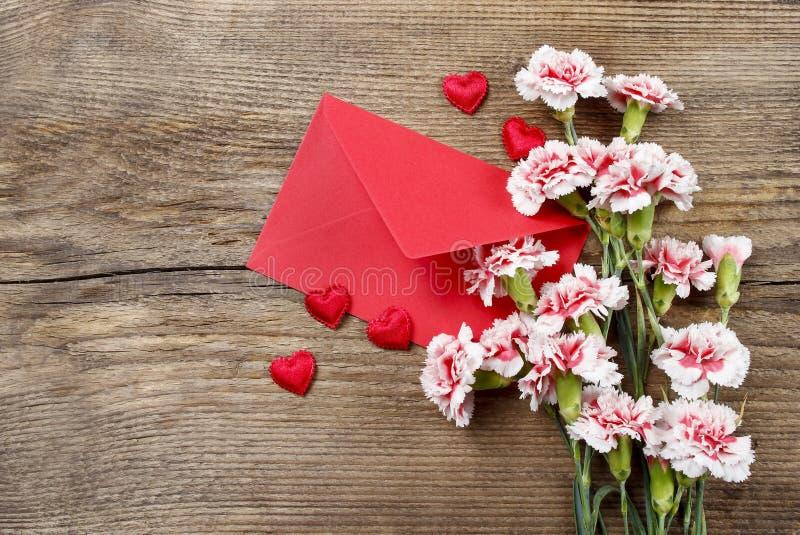 Oeillets roses, coeurs et enveloppe rouge image stock