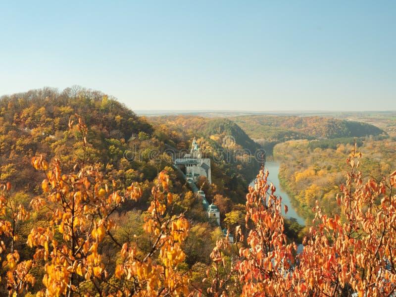 Oekraïens aardlandschap Klooster op heuvel Smalle rivier die onder de heuvels stromen Kleurrijk de herfstbos op heuvels stock foto
