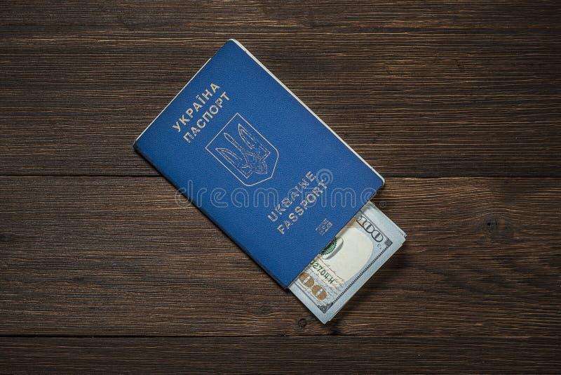 Oekraïens internationaal biometrisch paspoort met dollars op een houten achtergrond stock afbeeldingen