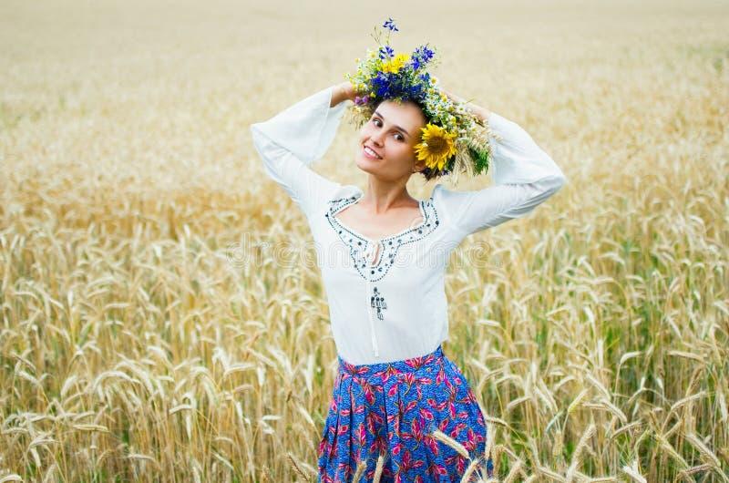 Oekraïens meisje in een mooie kroongangen door de de zomerweide Het meisje is gekleed in etnische kleren met stock afbeelding