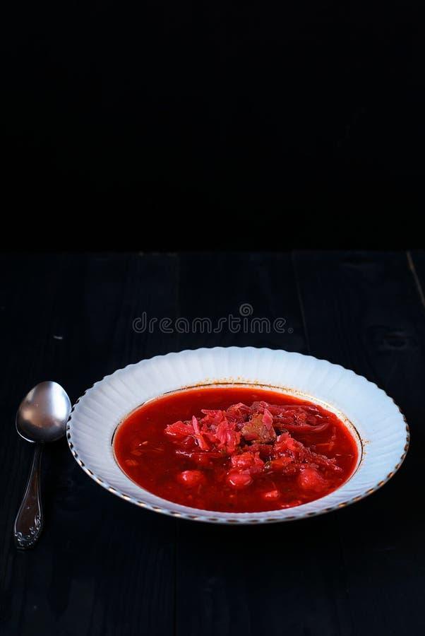 Oekraïense borscht op een zwarte achtergrond in een witte plaat stock fotografie