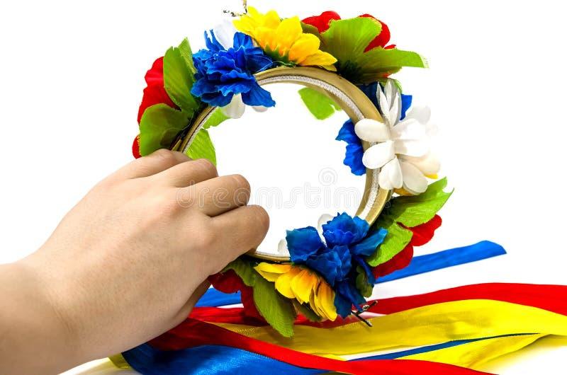 Oekraïense nationale kroon met kleurrijke linten in een vrouwelijke hand op een witte achtergrond stock afbeelding