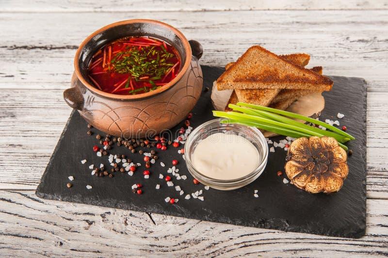 Oekraïense nationale schotel borscht De Russische borsjt in een kleipot met uien, saus, zure room, broodcroutons, roosterde knofl royalty-vrije stock foto