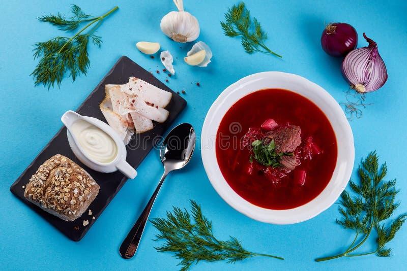 Oekraïense soepborsjt op blauwe kleurenachtergrond Borsjt met stuk van brood, zure room, reuzel en knoflook op zwarte schalie royalty-vrije stock foto's