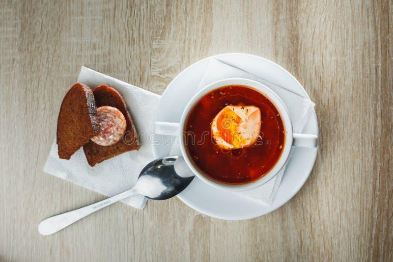 Oekraïense traditionele borsjt Russische vegetarische rode soep in witte kom op rode houten achtergrond Hoogste mening Borscht, b stock afbeelding