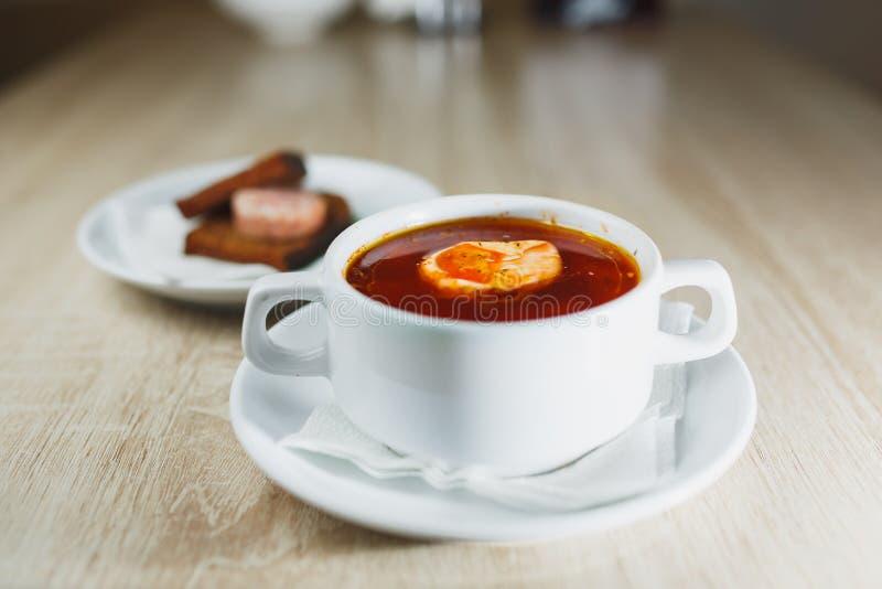 Oekraïense traditionele borsjt Russische vegetarische rode soep in witte kom op rode houten achtergrond Hoogste mening Borscht, b stock afbeeldingen