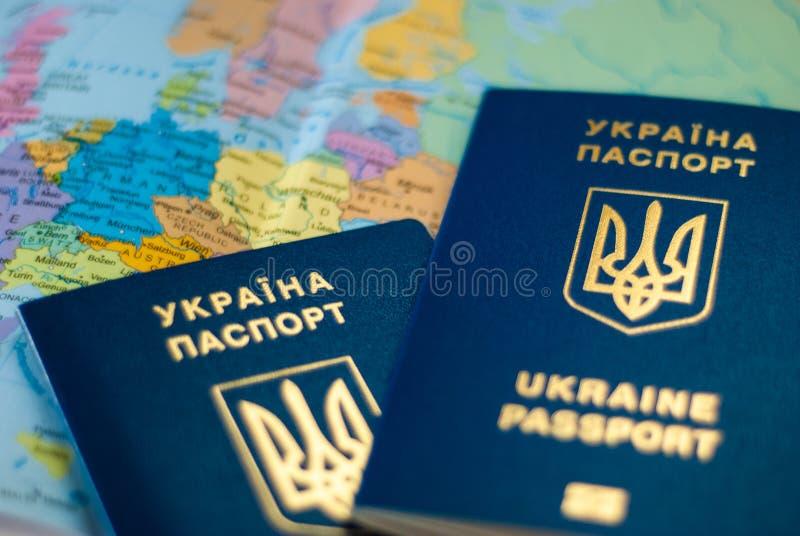 Oekra?ens internationaal biometrisch paspoort op een kaartachtergrond stock foto's