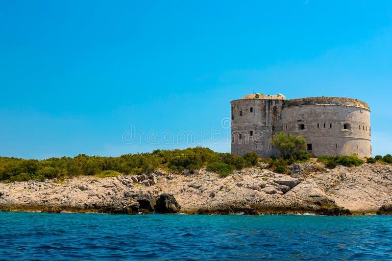 Oerhörd seascape Gammalt torn på en stenig kust vid havet, Boka-Kotor fjärd, royaltyfria bilder