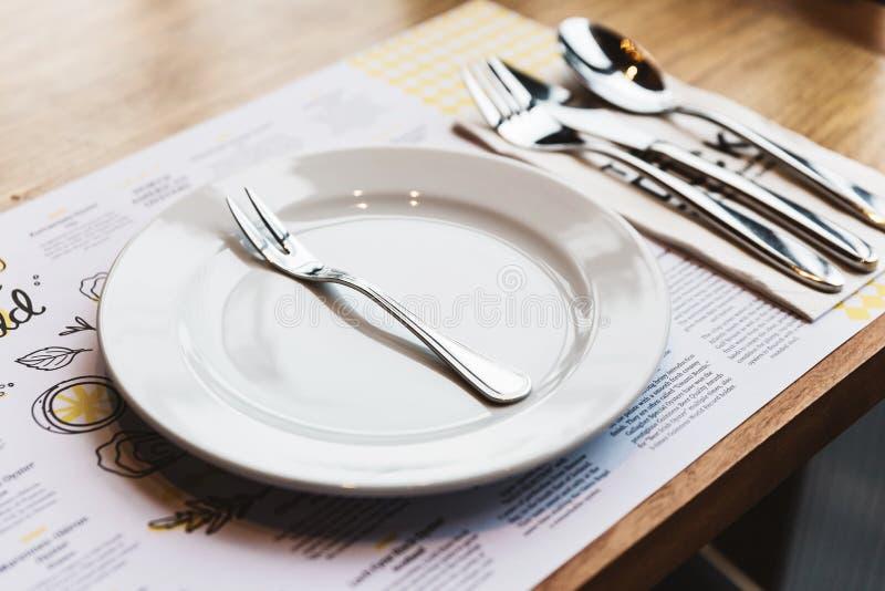 Oestervork met bestek: Lepel, Vork en Mes op witte ceramische plaat Zilver geplateerde voedselwaren stock fotografie