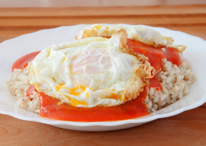 Oeuf au plat avec du riz trop cuit et la tomate image stock