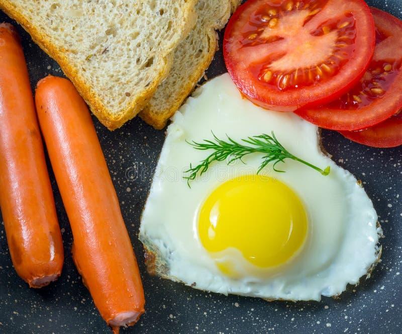 Oeuf au plat de petit déjeuner en saucisses en forme de coeur et grillées, tomates, pain, vue supérieure photographie stock libre de droits