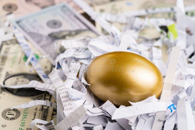 Oeuf d'or brillant dans le nid de papier avec des nombres financiers sur la pile de la m?taphore d'argent de billet de banque de  photographie stock