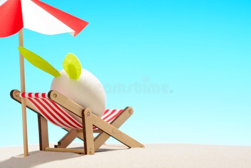 Oeuf de pâques avec des oreilles de lapin dans l'underumbrella de canapé sur la plage sablonneuse images stock