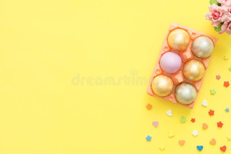 Oeuf de pâques coloré plat de vue supérieure de configuration peint en couleurs en pastel composition et fleurs de ressort sur le photos stock