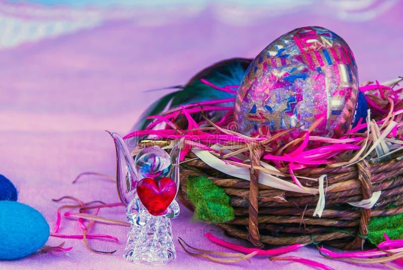 Oeuf de pâques décoratif dans l'ange de panier et en verre avec le coeur photo libre de droits