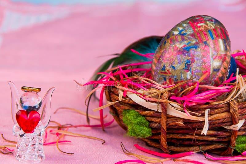 Oeuf de pâques décoratif dans l'ange de panier et en verre avec le coeur photographie stock