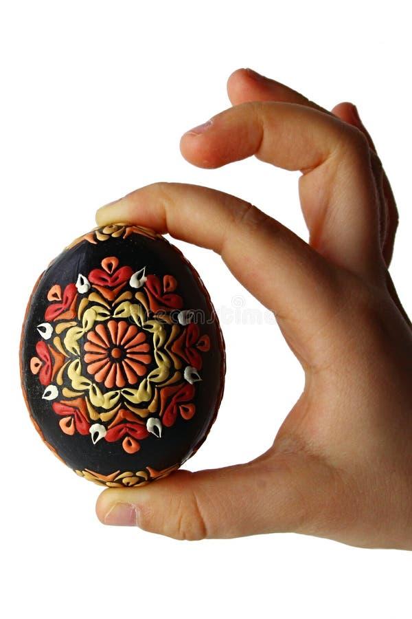 Oeuf de pâques fait main noir richement décoré des ornements traditionnels de fleur, tenus à disposition du petit enfant, fond bl image stock