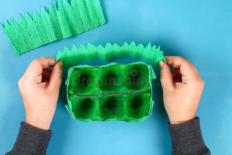 Oeuf de pâques de panier de DIY de plateau de carton, papier de crêpe, tige de chenille sur le fond bleu image libre de droits
