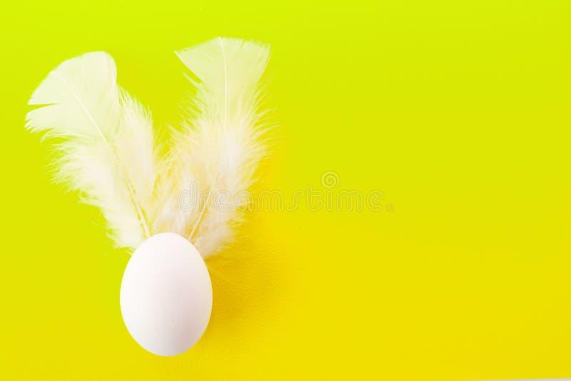 Oeuf de p?ques avec les plumes blanches jaune Copiez l'espace fond P?ques color?e images stock
