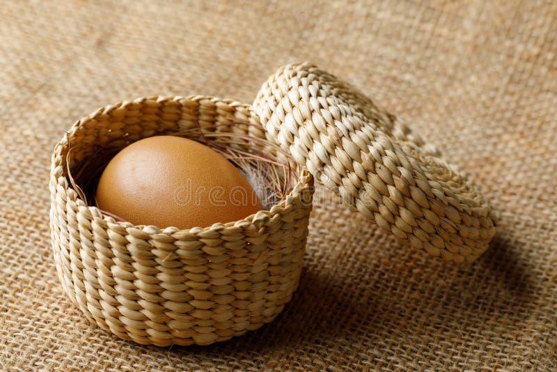 Oeuf de poulet ou de poule dans le panier en osier sur la toile à sac photographie stock libre de droits
