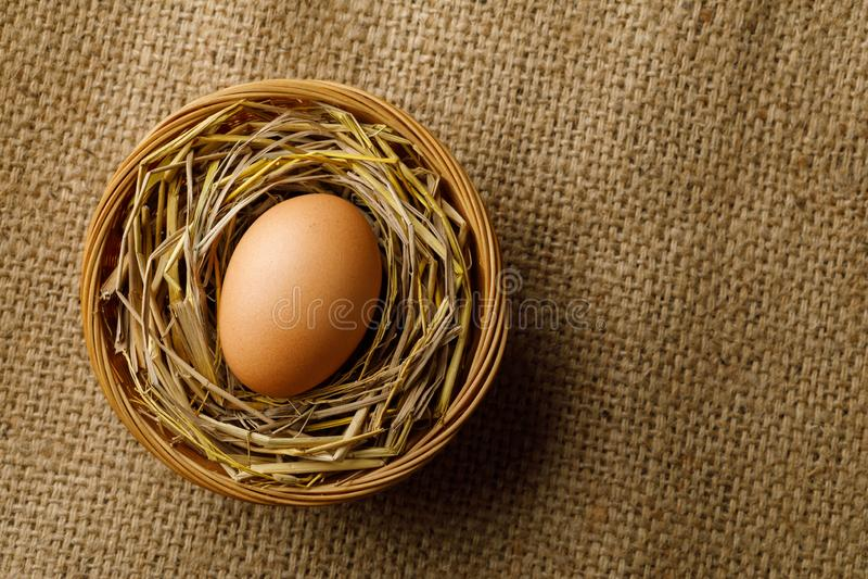 Oeuf de poulet ou de poule sur la paille dans le panier en osier sur la toile à sac photos stock
