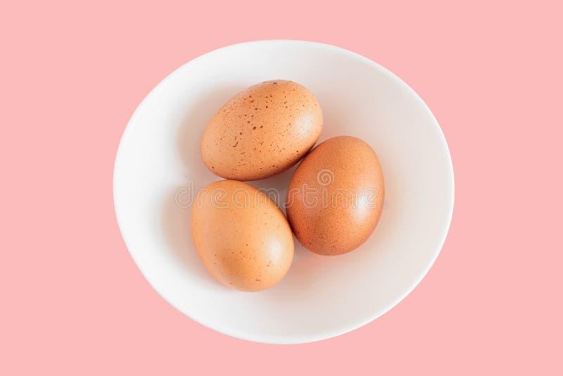 Oeuf de poulet, trois oeufs de poulet d'isolement sur le fond blanc de plat, plat blanc avec des oeufs de poulet sur le fond rose image libre de droits