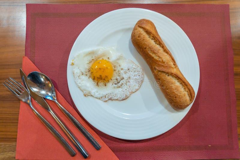 Oeuf et pain ensoleillés du plat blanc au restaurant photos stock