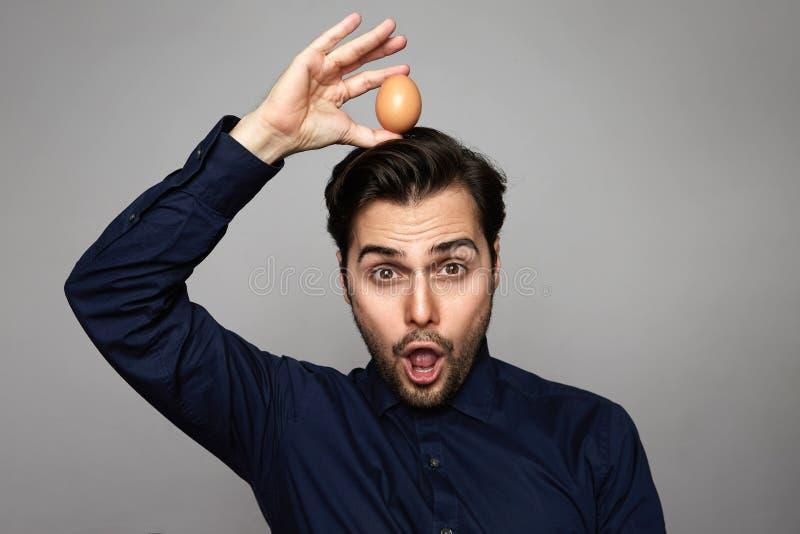 Oeuf organique frais d'homme de poulet hispanique attrayant de participation plus de tête sur le fond gris Fin vers le haut images libres de droits