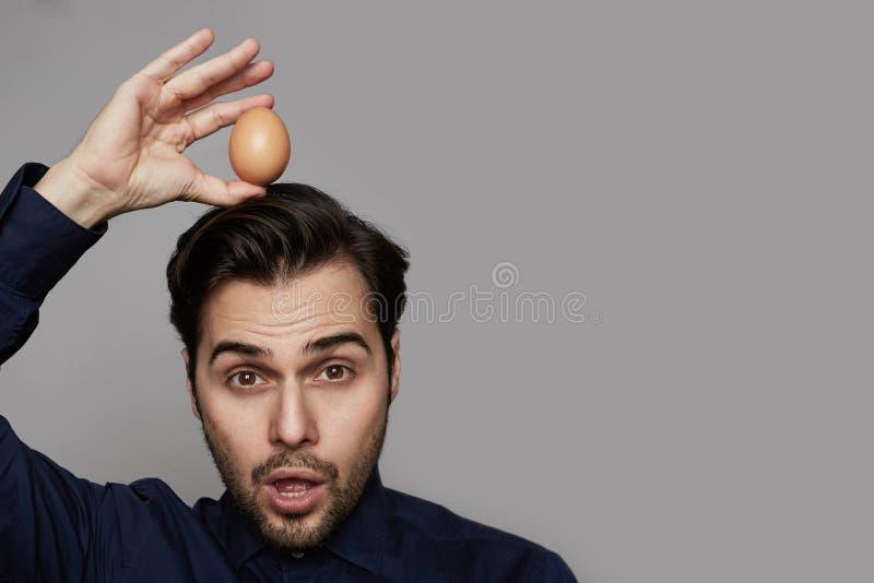 Oeuf organique frais d'homme de poulet hispanique attrayant de participation plus de tête sur le fond gris Fin vers le haut image libre de droits
