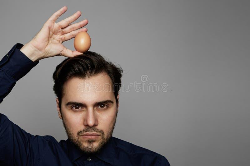 Oeuf organique frais d'homme de poulet hispanique attrayant de participation plus de tête sur le fond gris Fin vers le haut photographie stock libre de droits