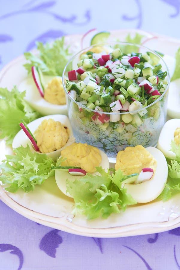 Oeufs à la coque avec de la salade, le concombre et le radis photographie stock libre de droits
