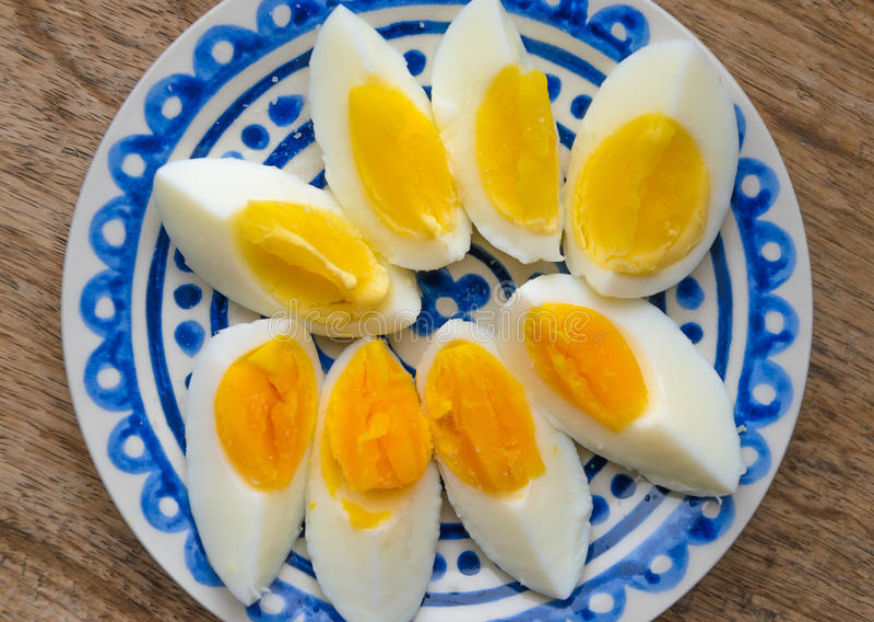 Oeufs à la coque coupés en tranches d'un plat décoré bleu photographie stock libre de droits