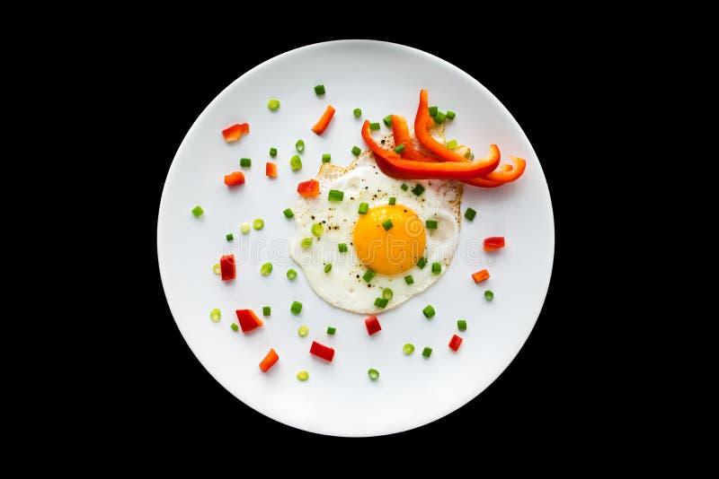 Oeufs au plat à l'oignon de germination et au paprika rouge sur un p blanc photos stock