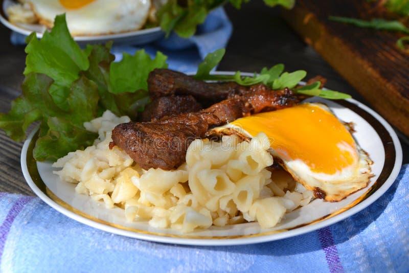 Oeufs au plat avec les pâtes et le fromage dans une poêle sur la table en bois, pâtes de Carbonara photographie stock libre de droits