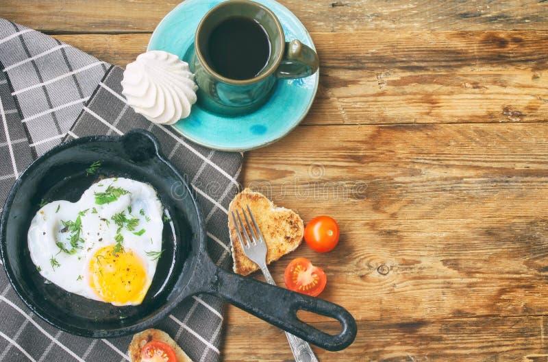 Oeufs au plat dans la poêle, forme de coeur de pain grillé, tasse de café photo stock