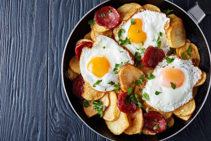 Oeufs au plat espagnols avec des pommes de terre et des saucisses photos stock