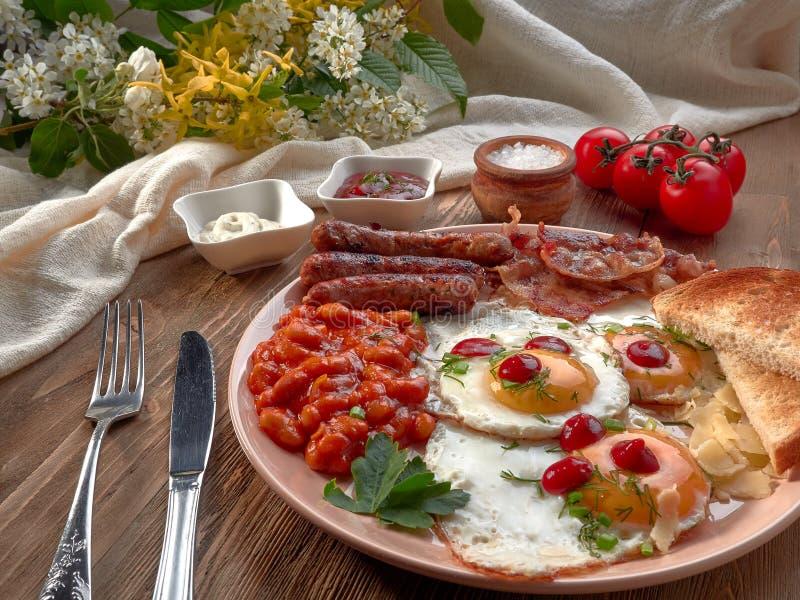 Oeufs au plat, haricots cuits, saucisses d?licieuses et pain grill? photographie stock libre de droits