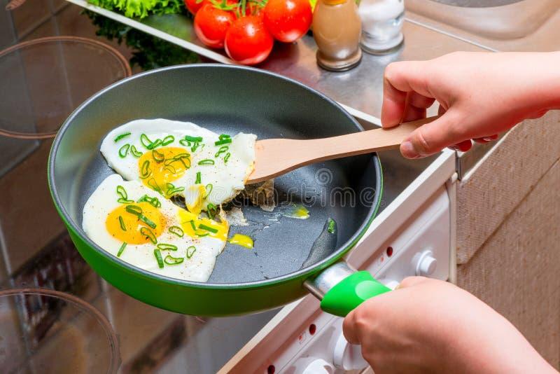 Oeufs au plat sur une gauffreuse, mains avec une spatule en bois photos libres de droits