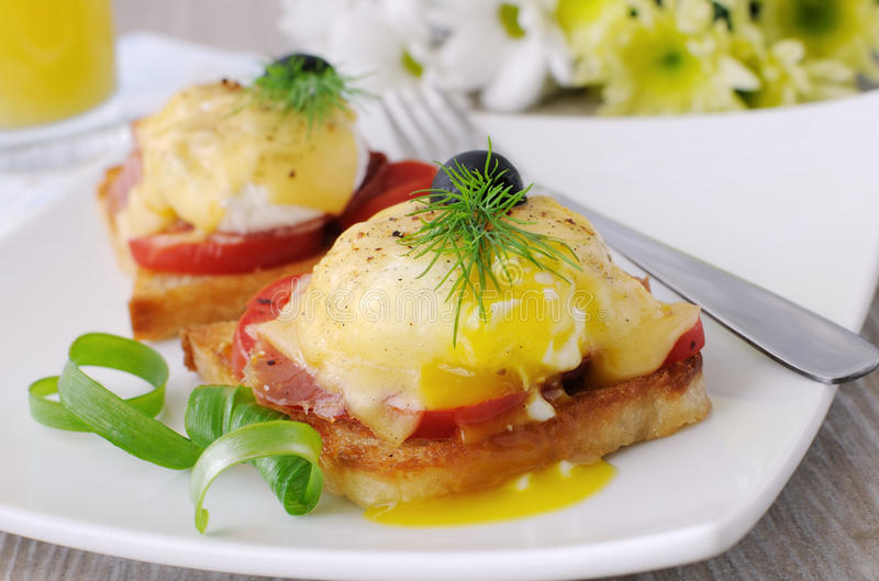 Oeufs Benoît avec du jambon et la tomate sur le pain grillé avec du fromage images stock