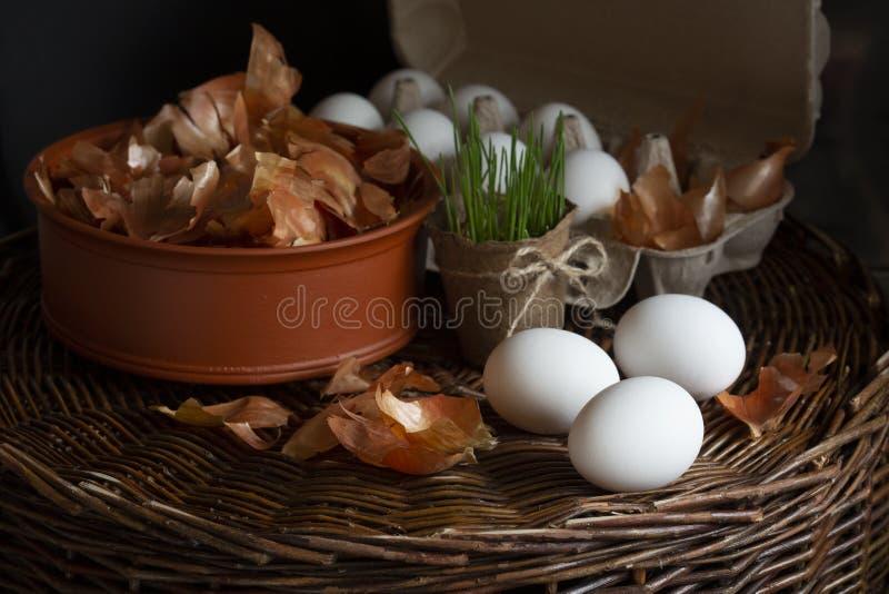 Oeufs blancs dans un carton avec une peau jaune d'oignon dans un plat sur un plateau en osier préparé pour la coloration image libre de droits