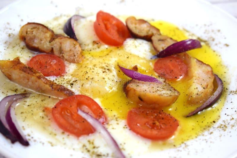 Oeufs brouillés délicieux avec des tomates et des saucisses photos stock