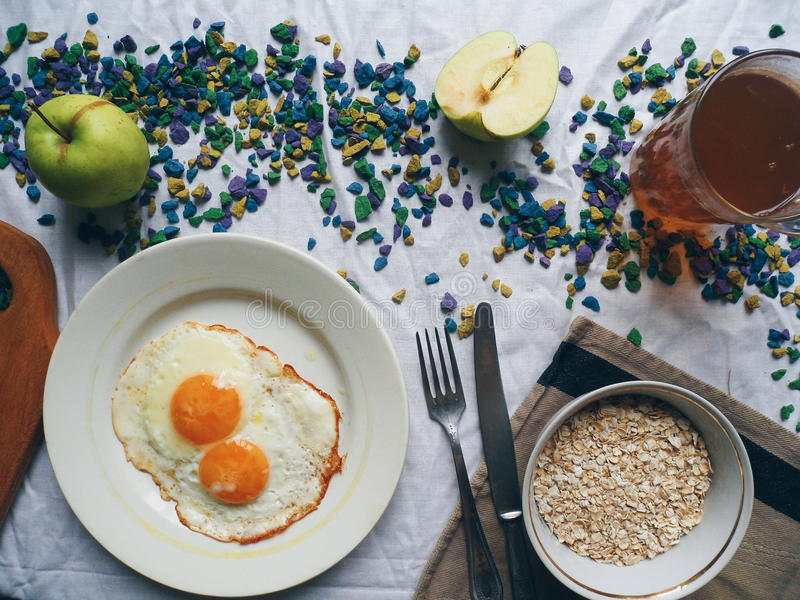 oeufs brouillés, farine d'avoine, pomme et tasse de thé sur la table image stock