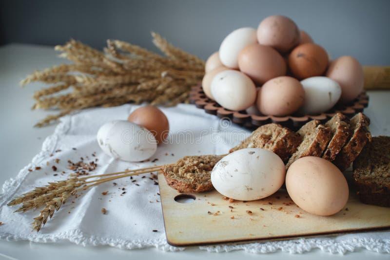 Oeufs bruns de poulet cru organique frais de la ferme et du pain chaud de grain avec des graines de lin R?gime sain image libre de droits