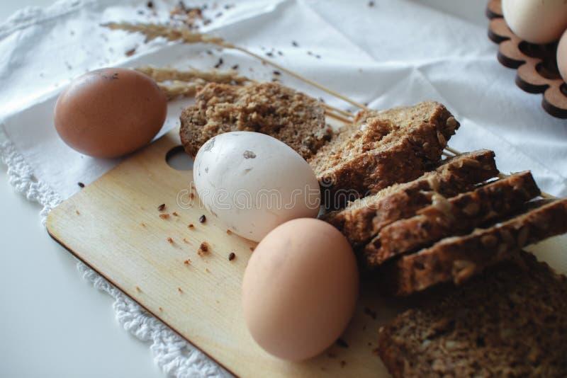 Oeufs bruns de poulet cru organique frais de la ferme et du pain chaud de grain avec des graines de lin R?gime sain photo libre de droits